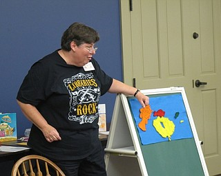 "Neighbors | Jessica Harker.Karen Saunders, the childrens librarian at Boardman library, uses magnetic fish on a chalk board to read ""Blue Sea,"" to the group of children gathered at the Family Story time July 11."