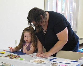 Neighbors | Jessica Harker.Shelli Smith helps her daughter, Elizabeth, age 3, create a net out of paper for the project portion of Family Story time at the Boardman library July 11.