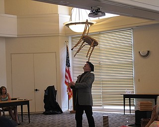 Neighbors | Jessica Harker.Michael Baldridge balanced a chair on his head during the July 24 Paper Magic event at the Austintown library.
