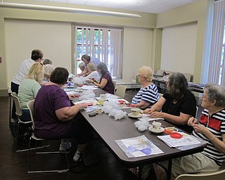 Neighbors | Natalie Wright.Participants of the Crazy Quilting program listened to instructions given by volunteers from the Youngstown Embroidery Guild before beginning their project on July 20.