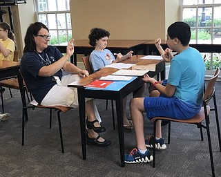 Neighbors | Jessica Harker.Librarian Karen Steed practiced signing her name with students on July 26 at the first ASL camp at the Poland library.