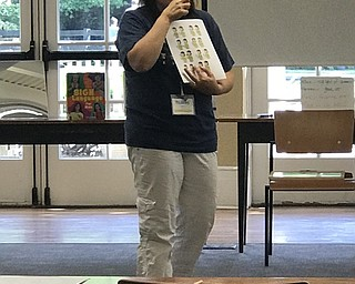 Neighbors | Jessica Harker.Librarian Karen Steed taught children the sign for orange at the Poland library ASL camp July 26.