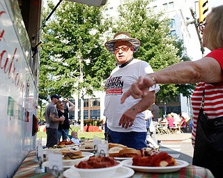 David Simon, of Youngstown, and Faye Berndt, right, of Canfield, look at some of the food being sold by Roberto's Italian Ristorante at the Greater Youngstown Italian Fest on Friday. EMILY MATTHEWS | THE VINDICATOR