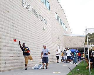 Gene Kelly, left, who went to Boardman high school and who's mother graduated from East High School in 1976, plays corn hole with Ramon Mercado, class of 1968, at the East High School Alumni Reunion on Saturday.