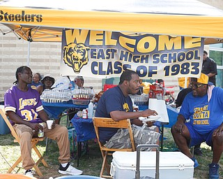 From left, Mark Hopkins, class of 1991, Anthony Howell, class of 1993, and Derrick Stredrick, class of 1976, talk and eat at the East High School Alumni Reunion on Saturday.