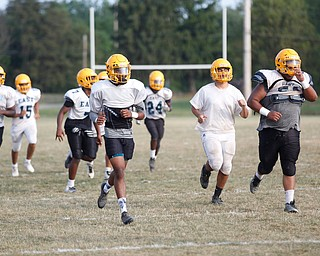 Zane Cylar, front left, warms up with his teammates at East High School's football practice Tuesday evening.