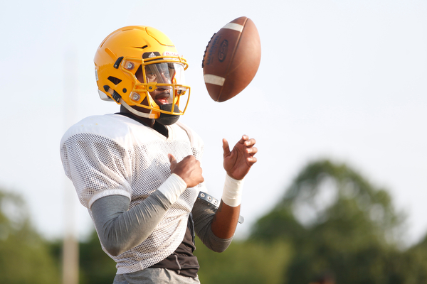 Zane Cylar tosses the ball in between practicing his throw at East High School's football practice Tuesday evening.