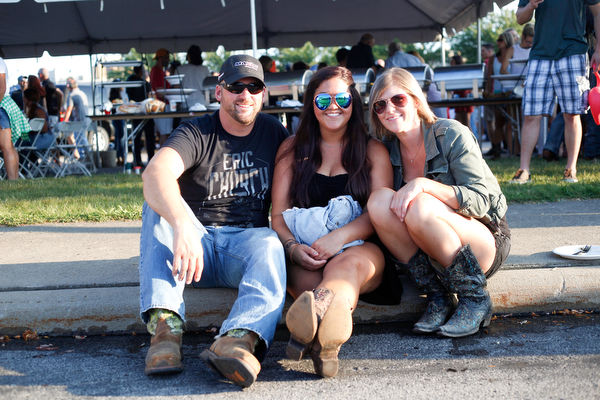 From left, Mark Cramer, of Liberty, Kelly Hyde, of Girard, and Carly Cramer, of Liberty, sit in the tailgating parking lot before the Florida Georgia Line concert on Saturday. EMILY MATTHEWS | THE VINDICATOR