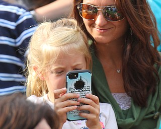William D. Lewis The Vindicator Audrey Jaskiewicz, 7, takes a photo while her mother Kris looks on at the Amp in Warren during a 8-13-18 YO YO MAH concert. They are from Vienna.