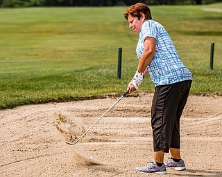 DIANNA OATRIDGE | THE VINDICATOR Diane Dofka hits her ball out of the bunker during the Ladies 2-player Championship of the Greatest Golfer of the Valley held at Trumbull Country Club in Warren on Wednesday.
