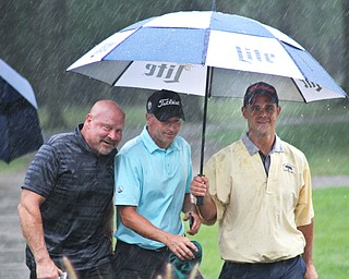William D. Lewis The Vindicator Heading for shelter during a rain delay at GGOV Friday at Mill Creek are from left: Jim DiMuzio, Mike Haggerty and John Rudolph.