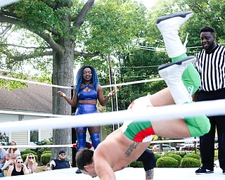 Wrestler Joseline Navarro watches as her opponent Mambo Italiano shows off his dance moves at the Latino Heritage Festival in Campbell on Saturday. EMILY MATTHEWS | THE VINDICATOR