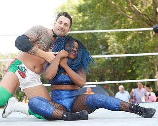 Wrestler Mambo Italiano puts his opponent Joseline Navarro in a headlock at the Latino Heritage Festival in Campbell on Saturday. EMILY MATTHEWS | THE VINDICATOR