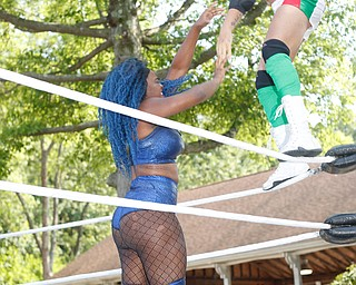 Wrestler Mambo Italiano,right, stands on the ropes above his opponent Joseline Navarro in a headlock at the Latino Heritage Festival in Campbell on Saturday. EMILY MATTHEWS | THE VINDICATOR