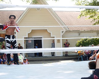 Wrestler Marc-Anthony Alejandro cheers for his teammate Calvin Couture as he wrestles at the Latino Heritage Festival in Campbell on Saturday. EMILY MATTHEWS | THE VINDICATOR