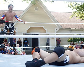 Wrestler Marc-Anthony Alejandro, left, cheers for his teammate Calvin Couture as he wrestles Dan Hooven at the Latino Heritage Festival in Campbell on Saturday. EMILY MATTHEWS | THE VINDICATOR
