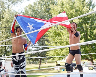 Wrestlers Marc-Anthony Alejandro and Calvin Couture hold up a Puerto Rican flag after their match against Cree Fudo and Dan Hooven at the Latino Heritage Festival in Campbell on Saturday. EMILY MATTHEWS | THE VINDICATOR