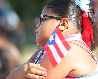 Jodairys Vasquez, 9, of Campbell, holds a Puerto Rican flag while watching wrestling at the Latino Heritage Festival in Campbell on Saturday. EMILY MATTHEWS | THE VINDICATOR