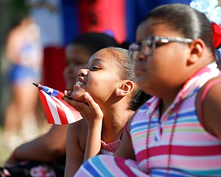 Adriana Holden, 10, of Campbell, holds a Puerto Rican flag while watching wrestling at the Latino Heritage Festival in Campbell on Saturday. EMILY MATTHEWS | THE VINDICATOR