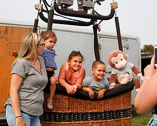 From Left, Amanda Vega, of Boardman, Veronica Vega, 2, Aaliyah Plourde, 5, of Brooklyn, and Damian Vega, 4, of Boardman smile in a hot air balloon basket as Esther Plourde, of Brooklyn, takes their photo at the Hot air balloon festival at Mastropietro Winery on Sunday..