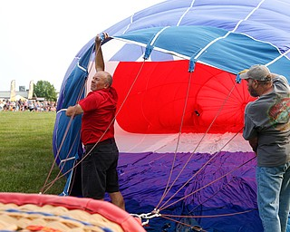 Rick Kohut, left, a hot air balloon pilot, and Chuck Evans, of Austintown, inflate a hot air balloon at the Hot air balloon festival at Mastropietro Winery on Sunday..