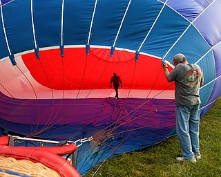 Rick Kohut, a hot air balloon pilot, walks inside a hot air balloon while Chuck Evans, of Austintown, holds it up while it inflates at the Hot air balloon festival at Mastropietro Winery on Sunday..