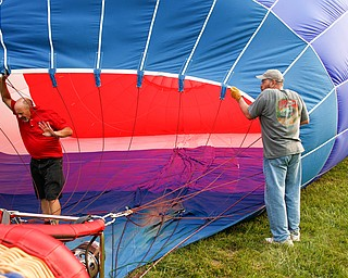 Rick Kohut, a hot air balloon pilot, walks out of a hot air balloon while Chuck Evans, of Austintown, holds it up while it inflates at the Hot air balloon festival at Mastropietro Winery on Sunday..