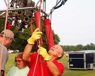 Rick Kohut, right, a hot air balloon pilot, gets his hot air balloon ready while Chuck Evans and Debbie Evans, both of Austintown, get in the basket at the Hot air balloon festival at Mastropietro Winery on Sunday. It was the Evans's 40th wedding anniversary..