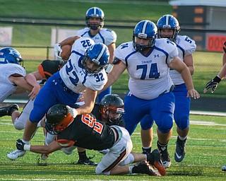 Poland running back Jake Rutana is brought down by a Marlington defender as teammate Jared Carcelli looks on in the BulldogsÕ 17-14 win Thursday night in Alliance...BOB ETTINGER | THE VINDICATOR