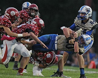 Ryan Slaven (30) of Western Reserve dives ahead for extra yardage as he is brought down by a group of Clipper defenders during Thursday night's matchup at Firestone Park in Columbiana. Dustin Livesay  |  The Vindicator  8/23/18  Columbiana