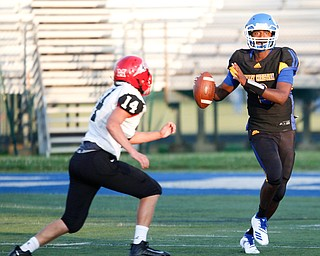 Valley Christian's Milan Square prepares to throw the ball as Campbell's Jake Armeni advances toward him during the first half of their game Saturday night at Dave Pavlansky Field in Poland. EMILY MATTHEWS | THE VINDICATOR