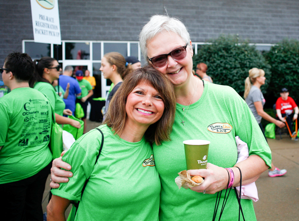 Friends and co-workers at Home Savings Janet Guerrieri, left, and Pat Barber, a breast cancer survivor, pose for a photo before the start of Panerathon outside of Covelli Centre on Sunday. .EMILY MATTHEWS | THE VINDICATOR
