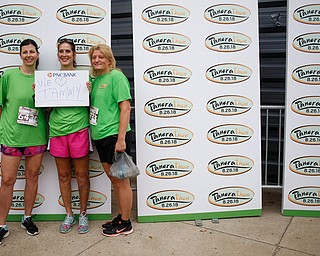 From left, Dawn Johnson, of Boardman, Debbie Rowder, of Austintown, and Lisa Galgozy, of Boardman, pose for a photo before the start of Panerathon outside of Covelli Centre on Sunday. Their sign is for Rowder's friend Tammy, who had a double mastectomy due to breast cancer..EMILY MATTHEWS | THE VINDICATOR