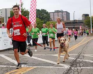 Dan Liptak, of Boardman, crosses the finish line with his golden doodle Charlie after running the 2-mile race at Panerathon outside of Covelli Centre on Sunday. .EMILY MATTHEWS | THE VINDICATOR