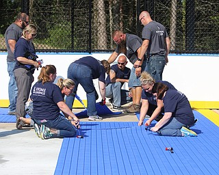 ROBERT K.YOSAY  | THE VINDICATOR..Mill Creek ParkÕs old ice skating rink is getting a blue makeover courtesy of a team that wears black and gold..On Tuesday morning, volunteers from Mill Creek MetroParks, Home Savings and Loan, the Youngstown Phantoms and The Pittsburgh Penguins Foundation were laying down blue tiles for the ParkÕs new dek hockey rink