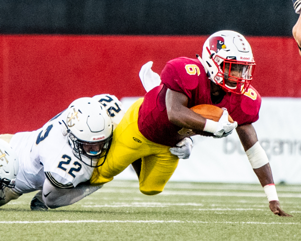 DIANNA OATRIDGE | THE VINDICATOR Cardinal Mooney's Dom Byrd is tackled by Akron Hoban's Luke Bauer after picking up a first down during their game at Stambaugh Stadium in Youngstown on Friday night.