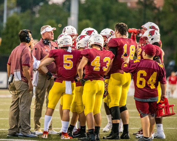 DIANNA OATRIDGE | THE VINDICATORÊ The Cardinal Mooney football team congregate during a time out in their game against Akron Hoban on Friday night at Stambaugh Stadium.