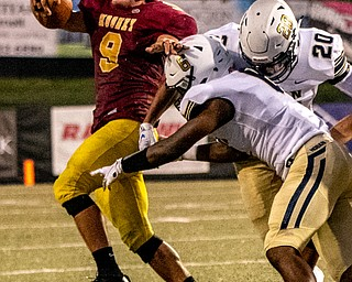 DIANNA OATRIDGE | THE VINDICATORÊ Cardinal Mooney's Jason Santisi tries to avoid the grasp of Akron Hoban's Montrell Jamison (20) and Alvin Stallworth (6) during their game at Stambaugh Stadium in Youngstown on Friday night.