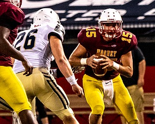 DIANNA OATRIDGE | THE VINDICATOR  Cardinal Mooney quarterback John Murphy evades the pursuit of Akron Hoban defender Matt Blanchard during their game at Stambaugh Stadium in Youngstown on Friday night.