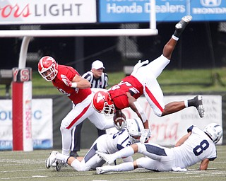 YSU's Tevin McCaster jumps over Butler players during the first half of the game on Saturday.