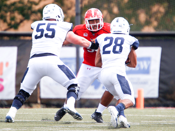 YSU's Wes Thompson attempts to block Butler's John McArthur (55) and Anthony Scaccia during the game on Saturday.
