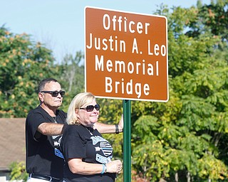 Justin Leo's parents Dave and Pat Leo stand next to the new sign of the bridge after it's unveiled at the dedication ceremony during which The Girard-McDonald viaduct was officially renamed the Officer Justin Leo Memorial Bridge on  Monday morning.