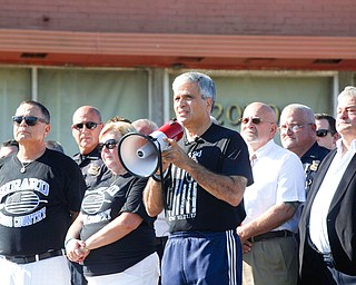 Girard Mayor James Melfi speaks during the dedication ceremony for the Justin A. Leo Memorial Bridge surrounded by Leo's parents, police office, and Girard community members Monday morning.