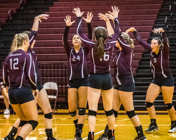 DIANNA OATRIDGE | THE VINDICATOR Boardman volleyball players celebrate after scoring a point on a block during their 3-2 victory against Austintown Fitch on Tuesday.