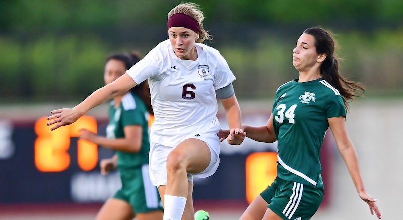 Boardman's Anna Deeley (6) eludes Ursuline's Lucia Rohrbaugh (34) while dribbling upfield during the second half of a game on Wednesday night at Youngstown State's Farmers National Bank Field. Deeley scored three goals and Boardman won, 7-0.