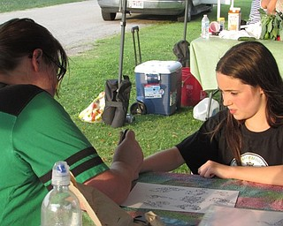 Neighbors | Submitted.A member of the LAOH drew historical Irish sybols on those who were interested at the Heritage Day event during the Austintown Farmers Market.