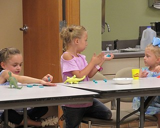 Neighbors | Jessica Harker.Children used play dough to make 'fossils' by pressing their plastic dinosaurs into it at the August 16 Sprout Club event at the Fellows Riverside Garden.