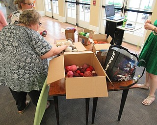 Neighbors | Jessica Harker .Boxes of yarn organized by color were available to project participants to use during the pompom door hanger making event August 20 at the Poland library.