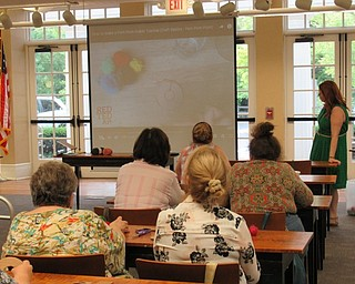 Neighbors | Jessica Harker .Event participants watch a video explaining how to make and use a pompom maker during the Summer Pompom Doorhanger making event August 20 at the Poland library.