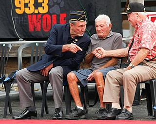 From left, Charles Jaros, a U.S. Army veteran of Vietnam, speaks to James Kenneally, a U.S.M.C veteran of Korea, and Roy Gallatin, a U.S.M.C veteran of World War ||, as Kenneally and Gallatin shake hands at the Austintown Patriot Day ceremony outside of Quaker Steak and Lube in Austintown on Thursday. EMILY MATTHEWS | THE VINDICATOR